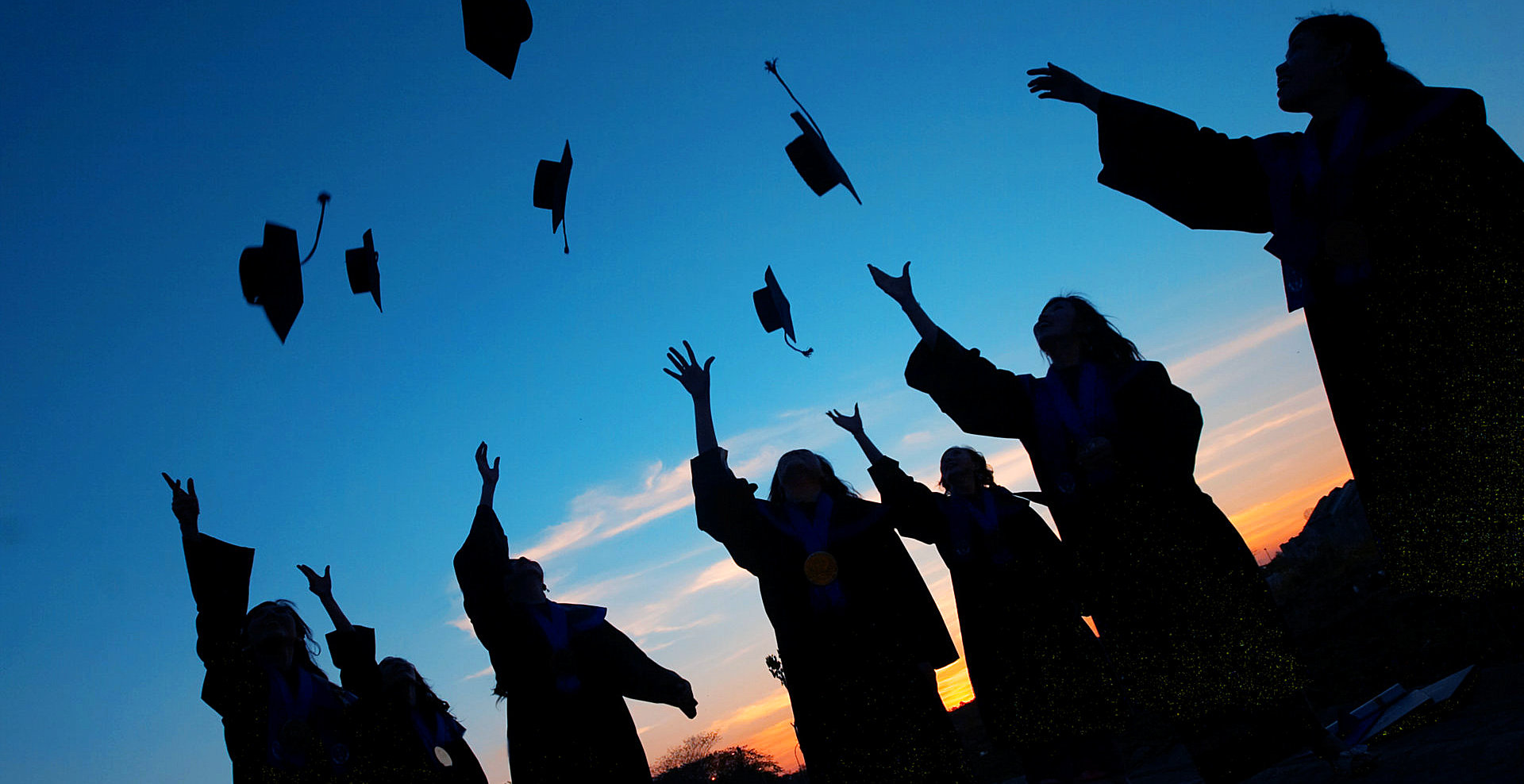 group of graduates throwing their graduation cup