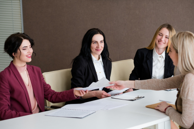 group of women from hr team smiling to a young work applicant during the interview
