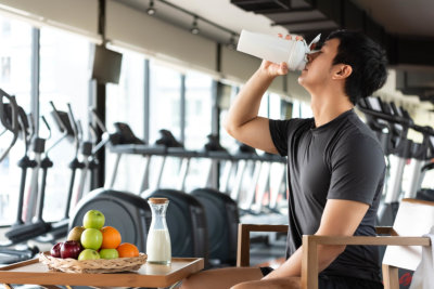 Handsome man drinking protein shake milk and many kind of fruits for nourishing body daily