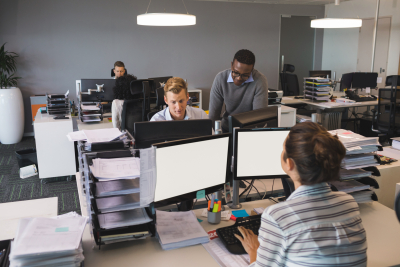 business colleagues working on computers at desk in office